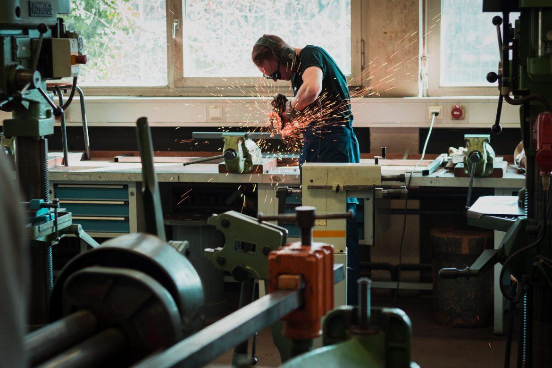 Man working hard grinding a piece of metal